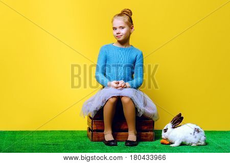 Cute smiling child girl sitting on a grass with Easter bunny and painted eggs. Easter holidays. Children's fashion. Happy yellow background.