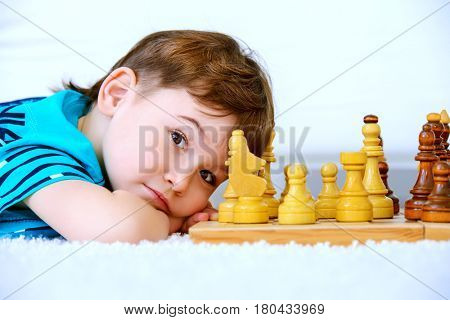 Little boy playing chess at home. Games and activities for children. Family concept.