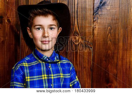 Portrait of a cute nine year old boy in a plaid shirt and cowboy hat over wooden background. Western style, cowboy. Kid's fashion. Clothes for children.