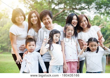 Group of cheerful Asian multi generations family portrait, grandparent, parent and children, outdoor nature park in morning with sun flare.