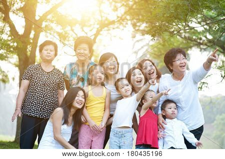 Large group of joyful Asian multi generations family portrait, grandparent, parent and children, outdoor nature park in morning with sun flare.