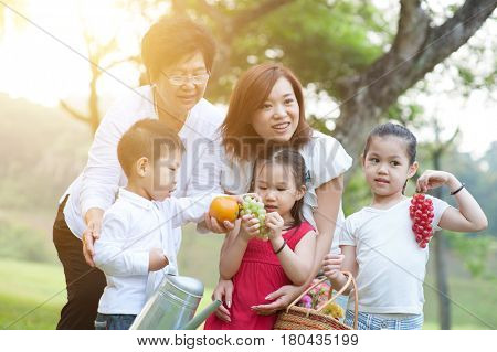 Candid portrait of joyful multi generations Asian family at nature park. Grandmother, mother and grandchildren outdoor fun. Morning sun flare background.