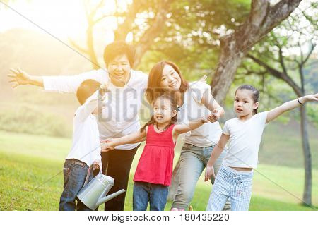 Candid portrait of happy multi generations Asian family at nature park. Grandmother, mother and grandchildren outdoor fun. Morning sun flare background.