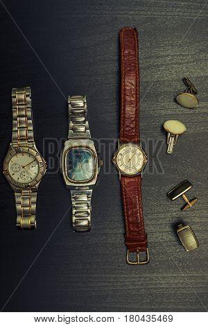 Different retro cufflinks and men's wristwatch over grey