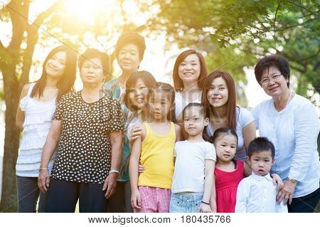 Large group of Asian multi generations family portrait, grandparent, parent and children, outdoor nature park in morning with sun flare.