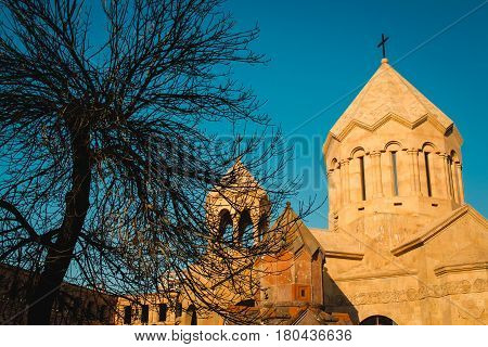 Photo of the Katoghike the oldest surviving church in Yerevan and new religious complex with Saint Anna Church. Architecture concept. City center. Armenia. Leafless tree. Medieval chapel