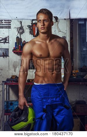 Sexy auto mechanic man stands on a background of tools holding a motorcycle helmet in his hand