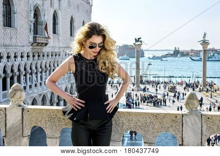 Young blonde female at San Marco square in Venice. Back view