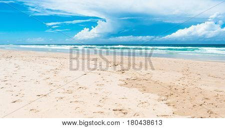 The beautiful view on the ocean and beach with turquoise sky and cumulus clouds in Gold Coast, Australia