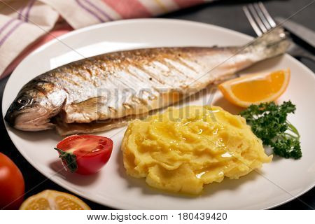 Grilled whole trout, mashed potato, lemon and parsley, close up