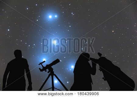 Couple looking at the stars with telescopes.