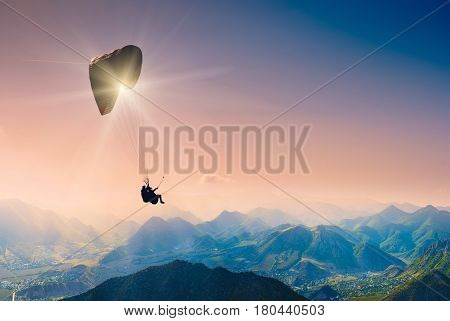Paraglide silhouette flying over the mountain peaks.