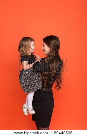 Beautiful young girl in a business suit and little girl in a black dress on a red background in the studio