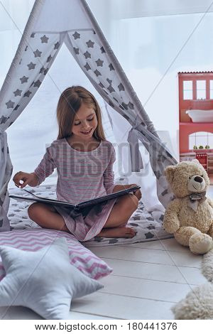 Lost in good book. Cute little girl reading a book and smiling while sitting on the floor in tent