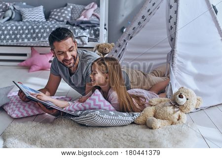 Family bonding. Father reading a book to his daughter while lying on the floor in bedroom