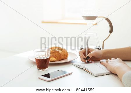 Woman sitting at table writing notes while having lunch. Morning routine. Enjoying free time.