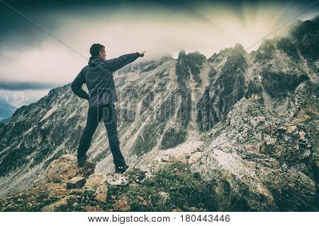 Hiker stays on a rocky ridge and point to the sunrise over the mountain. Caucasian Georgia Swaneti region.