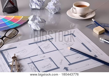 Drawing the interior of a house on the workbench of an engineer. With grey table and tools. Elevated view. Horizontal composition poster