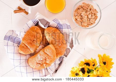 Breakfast with croissants and cup coffee on wooden table.