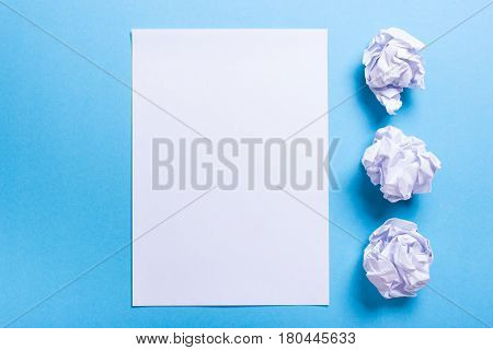 Crumpled paper ball and clean sheet on a blue background