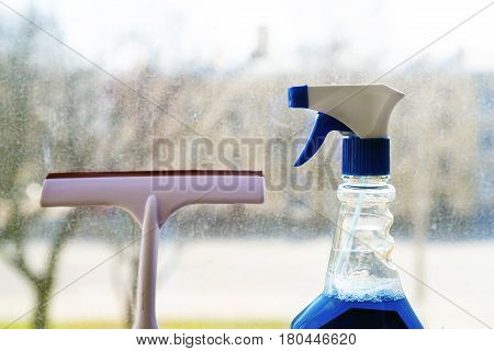 Tools for window cleaning. Cleaning spray and squeegee on a dirty window background.