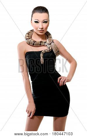 Vertical studio shot of a beautiful classy Asian young woman in a black dress smiling to the camera holding a snake on her shoulders isolated on white femininity sexuality sexy hot seductive exotic .