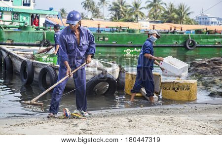 Phu Quoc, Vietnam - Mar 22, 2017: Local cleaners cleaning and carrying garbage on the beach shore of Phu Quoc island, Kien Giang province, south Vietnam.