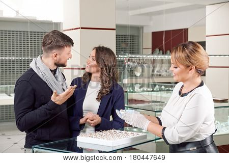 We found it Happy smiling couple looking at each other as the female jeweler showing them engagement rings