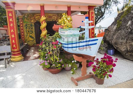Phu Quoc, Vietnam - Mar 19, 2017: Wooden boat displayed as a religious symbol at Dinh Cau temple, a famous religious view point on the island.