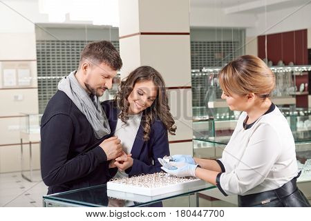 How about this one Happy young engaged couple inspecting rings at the jewelry store