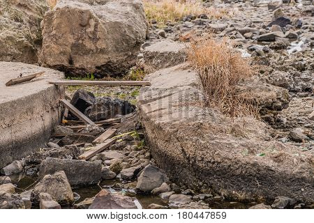 Scraps of wood and twine laying on ground among stones and other debris