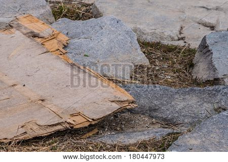 Closeup of a sheet of plywood on ground laying on top of large gray stones