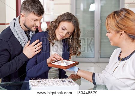 Try them. Female jeweler assisting young couple in choosing engagement rings
