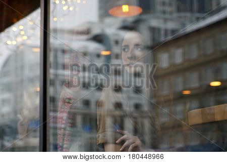 A troubled girl sits behind the window of cafe. She is concerned about something. She looks out for someone outside the window, a confused look. Window reflection.