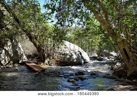 PALM SPRINGS, CA - MARCH 24, 2017: Tahquitz Canyon Creek bridge below the falls. Hikers must walk across stones and a small wooden foot bridge to cross the creek.