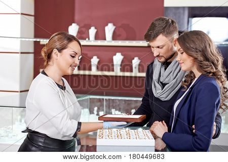 Special pieces. Professional jeweler showing jewelry variety of her store to a young loving couple