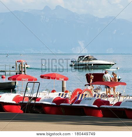 Lausanne Switzerland - August 26 2016: Catamarans on Lake Geneva in Lausanne Ouchy fishing village Switzerland. People on the background