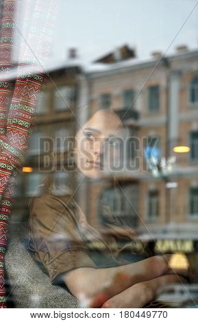 Young girl, loneliness in coffee shop. She looks out the window, lost in thought. The window displays old  house and office building. City life, window reflection, urban style