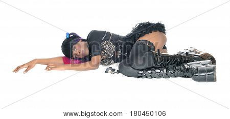 A young steam punk African American woman in a short skirt and long boots lying on the floor isolated for white background.