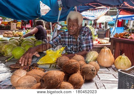 Victoria Mahe Seychelles - December 16 2015: Sellers offer fresh fruits in the Sir Selwyn Selwyn Clarke Market. Built in 1840 and renovated in 1999 it remains the bustling heart of the capital and definitely the best place to buy fresh fruits fish vegetab