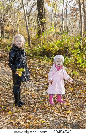little girls wearing rubber boots in autumnal nature