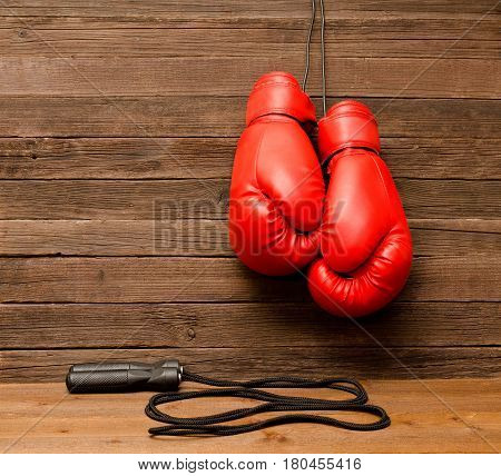 Two red boxing gloves hung on a wooden brown background jump rope