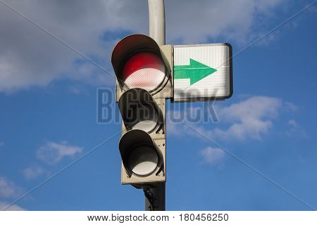 Traffic light and sign with arrow on sky background.