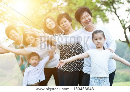Big group of happy Asian multi generations family playing at park, grandparent, parent and children, outdoor nature park in morning with sun flare.