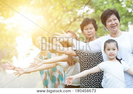 Big group of cheerful Asian multi generations family playing at park, grandparent, parent and children, outdoor nature park in morning with sun flare.