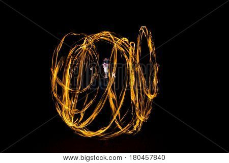 young woman dancing with fire poi making cirles