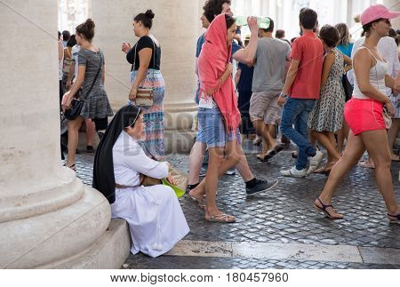 VATICAN CITY ITALY - July 26 2015: A nun sits to rest at the outskirts of St. Peter's Square as the crowd rushes by. The Vatican is a destination spot for clerics and tourists alike.
