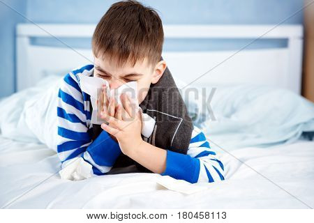 Ill boy lying in bed. sad child with fever blowing a nose