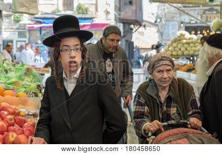 Undefined Orthodox Jewish Boy And Elderly Woman At Mahane Yehuda Market, Popular Marketplace In Jeru
