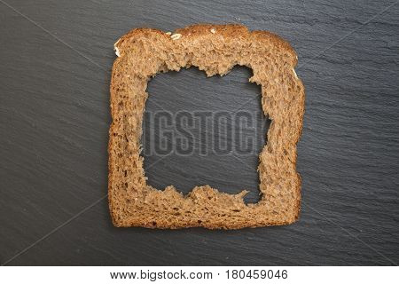 Whole Grain Sandwich Bread Slice With Hole, On Dark Surface/ Background.